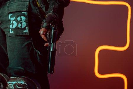 Photo pour Crochet vue d'un dangereux cyberpunk avec fusil sur fond noir avec éclairage au néon - image libre de droit