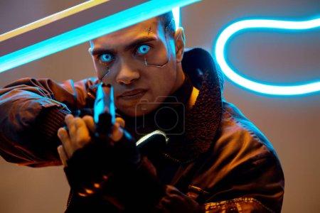 Photo pour La focalisation sélective d'un beau joueur de cyberpunk de races diverses avec des plaques métalliques sur le visage et des yeux bleus tenant un pistolet près de l'éclairage au néon - image libre de droit
