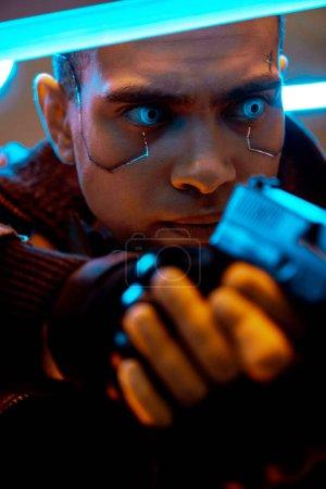 Photo pour Foyer sélectif d'un cyberpunk biracial avec des plaques métalliques sur le visage et des yeux bleus tenant une arme près de l'éclairage au néon - image libre de droit