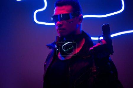 Photo pour Cyberpunk player in futuristic glasses holding gun near blue neon lighting - image libre de droit