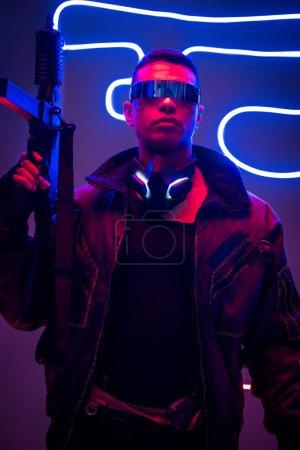 Photo pour Cyberpunk player in futuristic glasses holding gun near neon lighting - image libre de droit