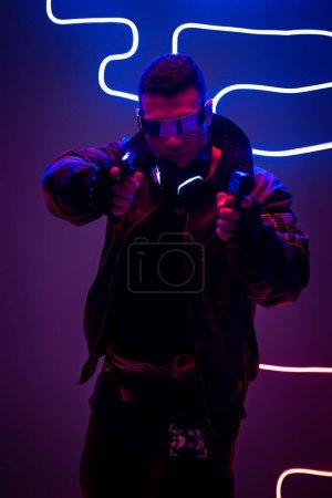 Photo pour Beau joueur de cyberpunk de race mixte dans des lunettes futuristes tenant un fusil près de l'éclairage au néon - image libre de droit