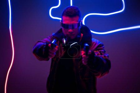 Photo pour Focus sélectif of mixed race cyberpunk player in futuristic glasses holding guns near neon lighting - image libre de droit