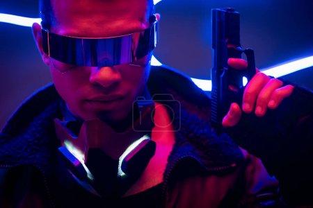 Photo pour Beau joueur de cyberpunk de race mixte dans des lunettes futuristes tenant un fusil près d'un éclairage au néon bleu - image libre de droit