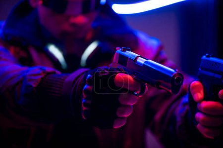 Photo for Selective focus of bi-racial cyberpunk player holding guns near neon lighting - Royalty Free Image