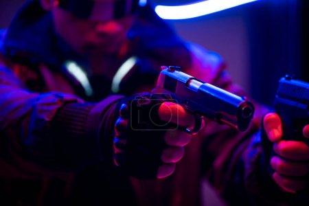 Photo pour Focus sélectif of bi-racial cyberpunk player holding gun near neon lighting - image libre de droit
