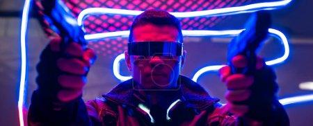 Photo pour Photo panoramique d'un joueur de cyberpunk de races diverses dans des lunettes futuristes tenant des fusils près de l'éclairage au néon - image libre de droit