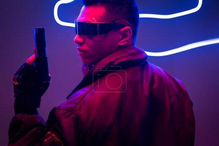Photo pour Side view of mixed race cyberpunk player in futuristic glasses holding gun near neon lighting - image libre de droit