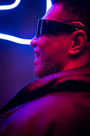 Photo for Happy mixed race cyberpunk player in futuristic glasses smiling near neon lighting - Royalty Free Image