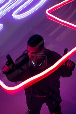 Photo for Overhead view of armed bi-racial cyberpunk player holding guns near neon lighting - Royalty Free Image