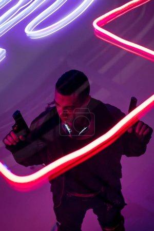 Photo pour Vue aérienne d'un cyberpunk armé et biracial tenant des armes à feu près de l'éclairage au néon - image libre de droit