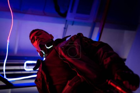 Photo for Low angle view of mixed race cyberpunk player standing near blue neon lighting - Royalty Free Image