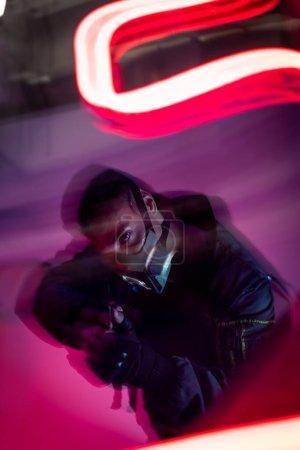Photo pour Flou de mouvement du cyberpunk armé bi-racial joueur dans le masque tenant pistolet près de néon rouge éclairage - image libre de droit