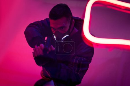 Photo for Overhead view of armed bi-racial cyberpunk player in mask holding gun near neon lighting - Royalty Free Image