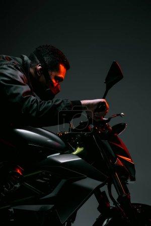 Photo pour Side view du joueur de cyberpunk de race mixte en masque moto à cheval sur gris - image libre de droit