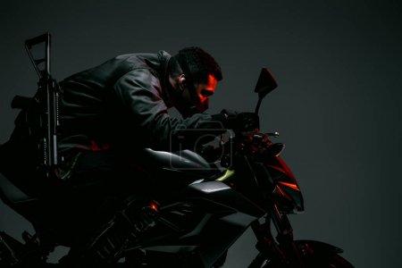 Photo pour Profil d'un cyberpunk biracial armé en masque moto à cheval sur gris - image libre de droit