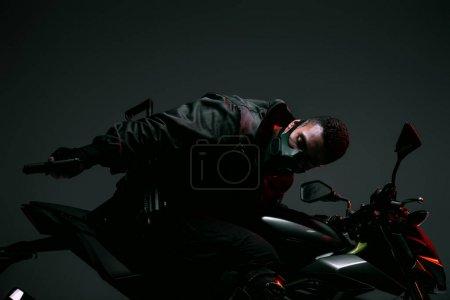 Foto de Jugador ciberpunk biracial armado en motocicleta a máscara y con arma en gris. - Imagen libre de derechos