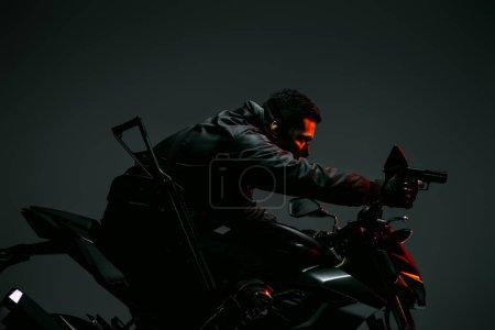 Photo pour Profil d'un cyberpunk biracial armé dans un masque de moto et tenant une arme sur le gris - image libre de droit