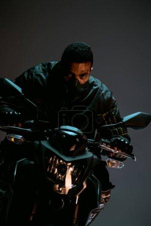 Photo pour Beau métissage cyberpunk player en masque moto à cheval sur gris - image libre de droit