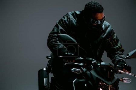 Foto de Jugador mixto de cyberpunk de carrera en máscara y gafas futuristas que montan motocicletas en gris. - Imagen libre de derechos