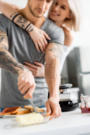 Selective focus of tattooed man cutting butter near smiling girlfriend in kitchen