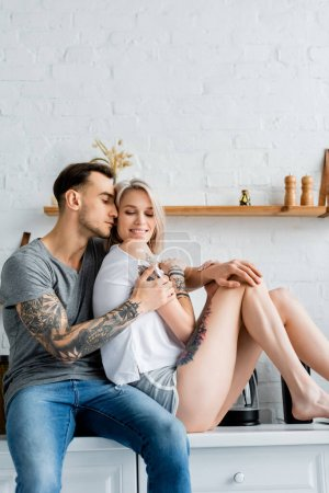Photo for Attractive smiling woman sitting on kitchen worktop near handsome tattooed boyfriend - Royalty Free Image