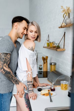 Photo for Side view of tattooed man touching hip of sensual blonde girl near breakfast on kitchen worktop - Royalty Free Image