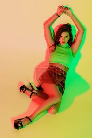 top view of sensual, fashionable girl looking at camera while lying on yellow background with green and red shadows