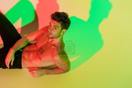 Photo pour Sexy, homme torse nu regardant la caméra tout en étant couché sur jaune avec des ombres rouges et vertes - image libre de droit