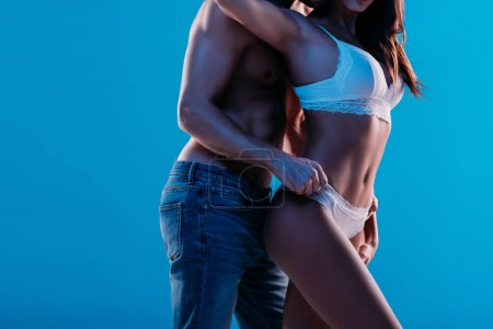 Photo for Cropped view of shirtless man touching panties of sexy girl isolated on blue - Royalty Free Image