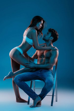 Photo for Sexy, shirtless man sitting on chair while seductive girl in white lingerie hugging him on blue background - Royalty Free Image