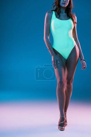 Photo pour Vue recadrée de fille sexy en maillot de bain et sandales à talons hauts posant sur fond bleu - image libre de droit