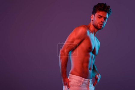 Photo for Sexy, confident man holding hand in back pocket while posing isolated on purple - Royalty Free Image