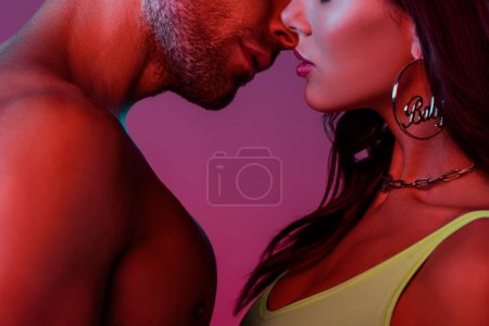 Photo for Cropped view of sexy young couple standing face to face on purple background - Royalty Free Image
