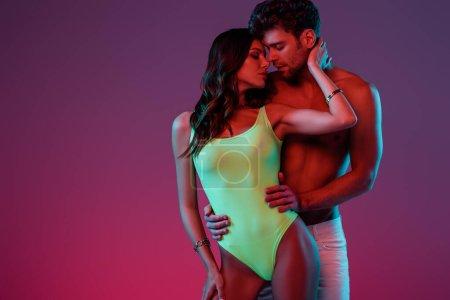 Photo pour Bel homme torse nu étreignant fille sexy en maillot de bain touchant son cou sur fond violet avec dégradé - image libre de droit