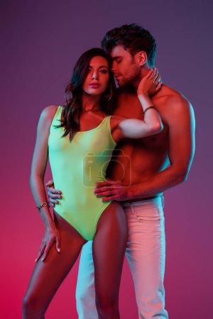 Photo pour Un homme sans chemise en jeans blancs Une fillette séduisante en maillot de bain touchant le cou sur fond violet - image libre de droit