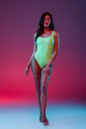 beautiful girl in neon green swimsuit and high heeled sandals standing on blue on purple background with gradient