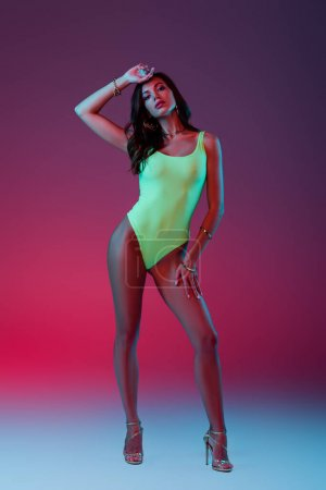 full length view of sexy girl in neon green swimsuit and high heeled sandals standing on blue on purple background with gradient