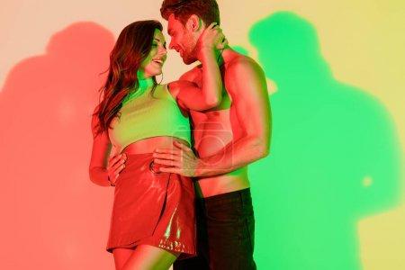 Photo pour Homme sexy et sans chemise touchant les hanches d'une fille sexy et élégante embrassant son cou sur un fond jaune avec des ombres rouges et vertes - image libre de droit