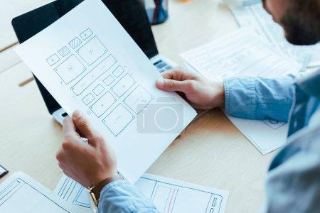 Photo pour Vue partielle d'un travailleur de la TI tenant des documents près d'un ordinateur portatif à table dans un espace de travail en commun - image libre de droit