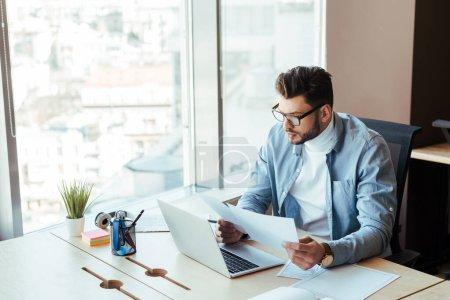 Photo pour Vue à grand angle d'un travailleur en TI concentré regardant des documents près d'un ordinateur portatif à une table dans un espace de travail commun - image libre de droit