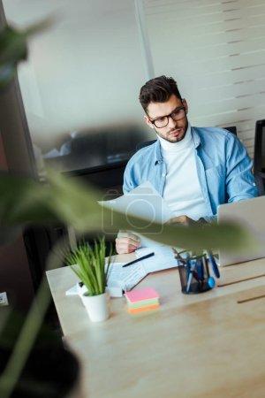 Photo pour Point de mire sélectif d'un travailleur en TI concentré tenant les documents et regardant l'ordinateur portatif sur une table dans un espace de travail commun - image libre de droit