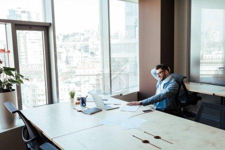 Foto de Vista de gran angular de los trabajadores de TI sentados a la mesa en el espacio de trabajo. - Imagen libre de derechos