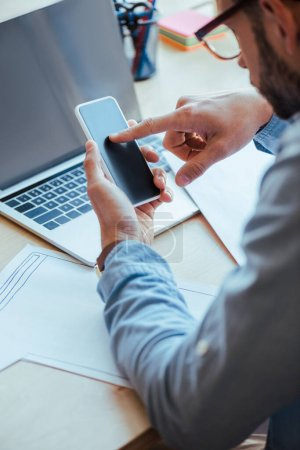 Photo for Selective focus of IT worker using smartphone at table with laptop and papers - Royalty Free Image