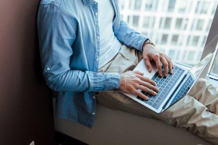 Photo pour Vue recadrée du travailleur informatique en utilisant un ordinateur portable sur le rebord de la fenêtre près de la fenêtre - image libre de droit