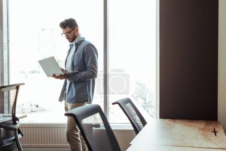Photo for IT worker with laptop near windows in coworking space - Royalty Free Image