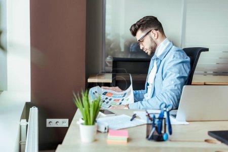 Photo pour Concentration sélective du concepteur de l'interface utilisateur regardant du papier tissé à la table - image libre de droit