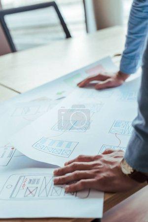 Photo pour Vue partielle du concepteur de l'interface utilisateur avec des papiers tissés à la table - image libre de droit