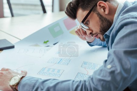 Photo for Selective focus of concentrated UI designer in glasses looking at wove papers - Royalty Free Image