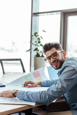 Photo pour UI designer souriant et regardant la caméra avec des papiers tissés à la table - image libre de droit